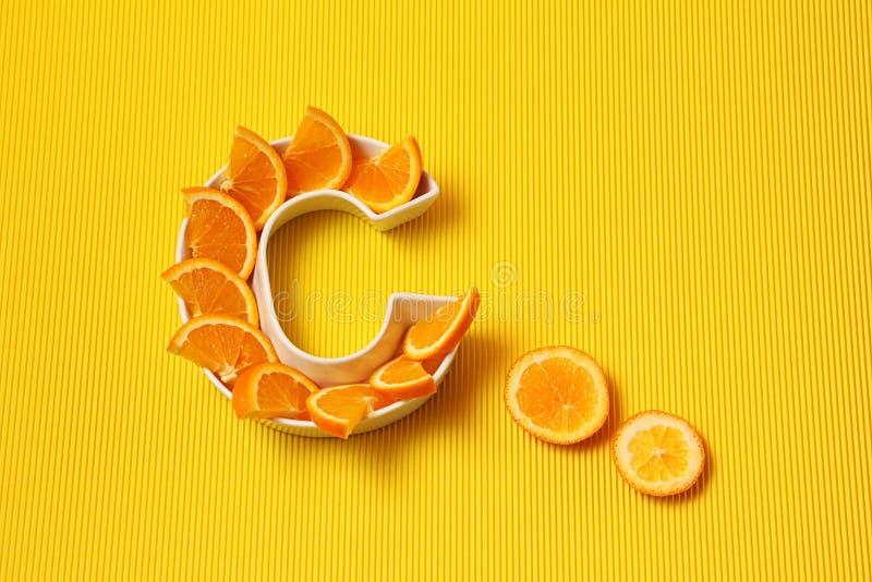 Vitamina C en concepto de la comida Placa en la forma de la letra C con las rebanadas anaranjadas en fondo amarillo brillante El  fotos de archivo