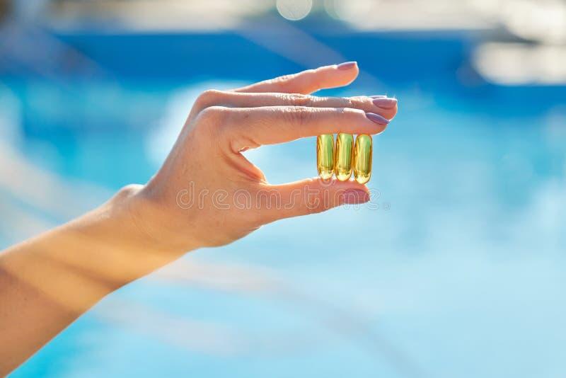 Vitamina D, E, A óleo de peixe cápsulas óleo de fígado de bacalhau ômega 3 na mão feminina fotos de stock
