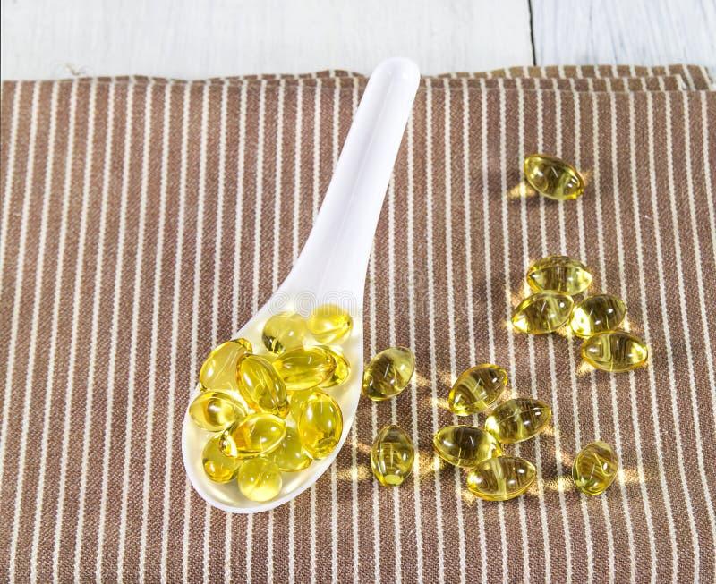 Vitamina dos peixes do óleo na colher branca imagens de stock royalty free