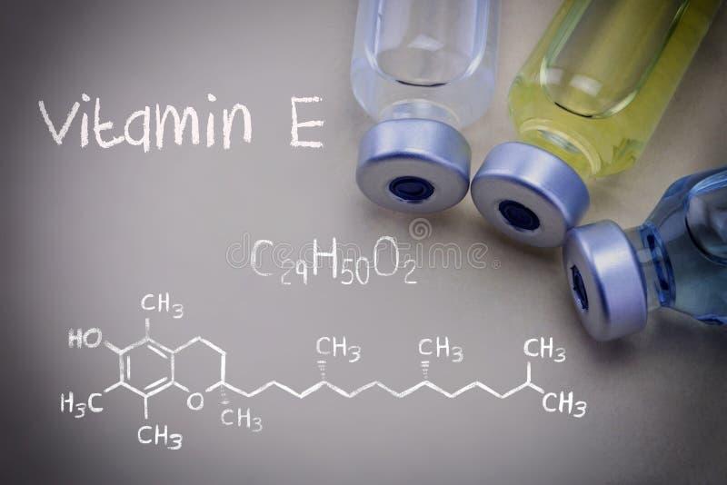 Vitamina química E da fórmula junto com tubos de ensaio diferentes imagens de stock royalty free