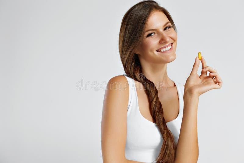Vitaminas Comer saudável Menina feliz com os tampões do óleo de peixes Omega-3 fotos de stock royalty free