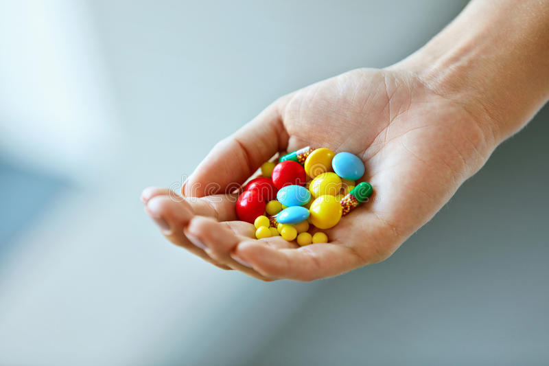 Vitaminas e suplementos Mão fêmea com comprimidos coloridos fotografia de stock royalty free