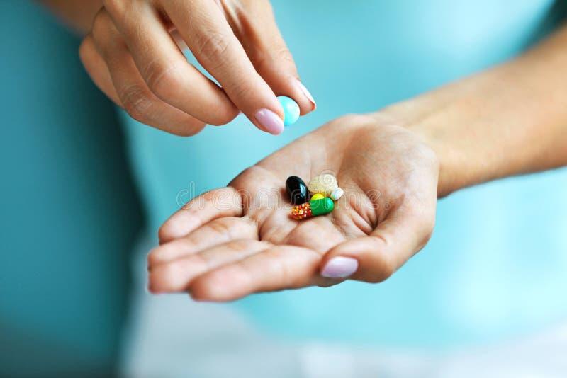 Vitaminas e suplementos Mão fêmea que guarda comprimidos coloridos foto de stock