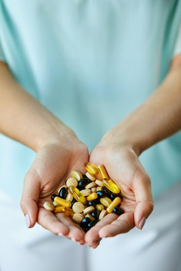 Vitaminas e suplementos A mulher entrega completamente de comprimidos da medicamentação imagens de stock royalty free
