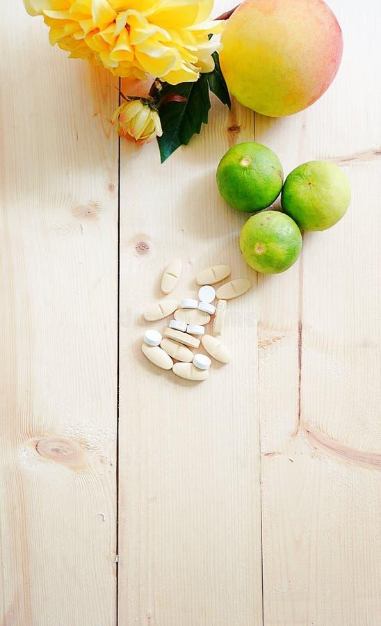 Vitaminas e suplementos no fundo de madeira da tabela com espaço da cópia, variedade de comprimidos da droga foto de stock