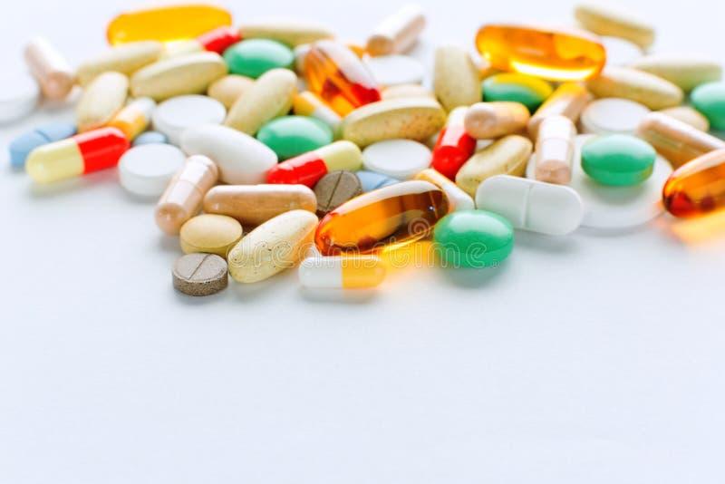 Vitaminas, ômega 3, óleo de fígado de bacalhau, suplemento dietético e tabuletas uma terraplenagem em um fundo claro fotografia de stock