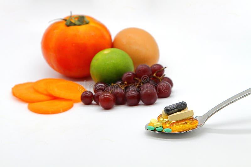 Vitaminas sortidos e suplementos nutritivos na colher do serviço no fundo colorido dos frutos do borrão imagens de stock royalty free