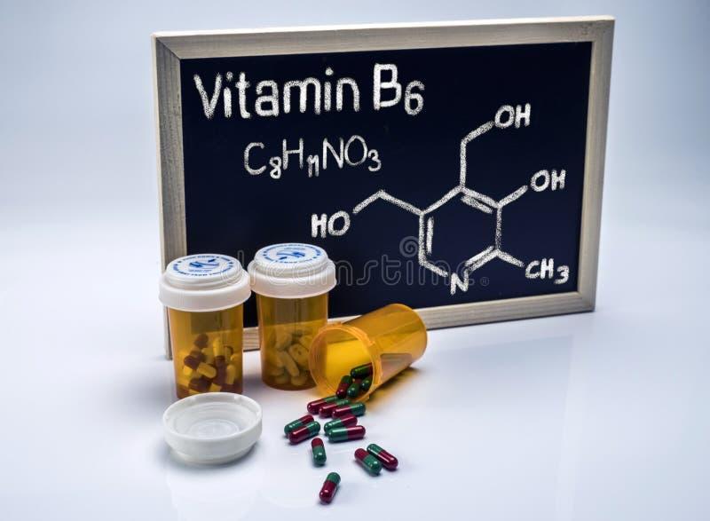 Vitamine B6 écrite à la main sur un tableau blanc à côté des bouteilles de capsules images stock