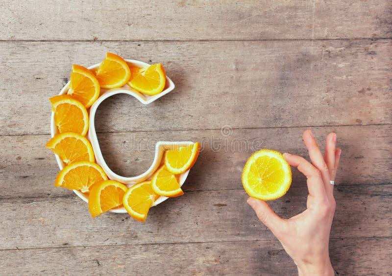 Vitamine C of ascorbinezuurvoedingsmiddel in voedselconcept Plaat in vorm van brief C met oranje plakken en de hand van de vrouw  royalty-vrije stock foto's