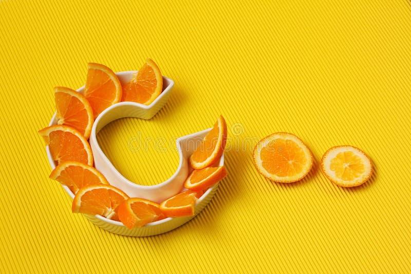 Vitamine C of ascorbinezuurvoedingsmiddel in voedselconcept Plaat in vorm van brief C met oranje plakken op heldere gele achtergr royalty-vrije stock afbeeldingen