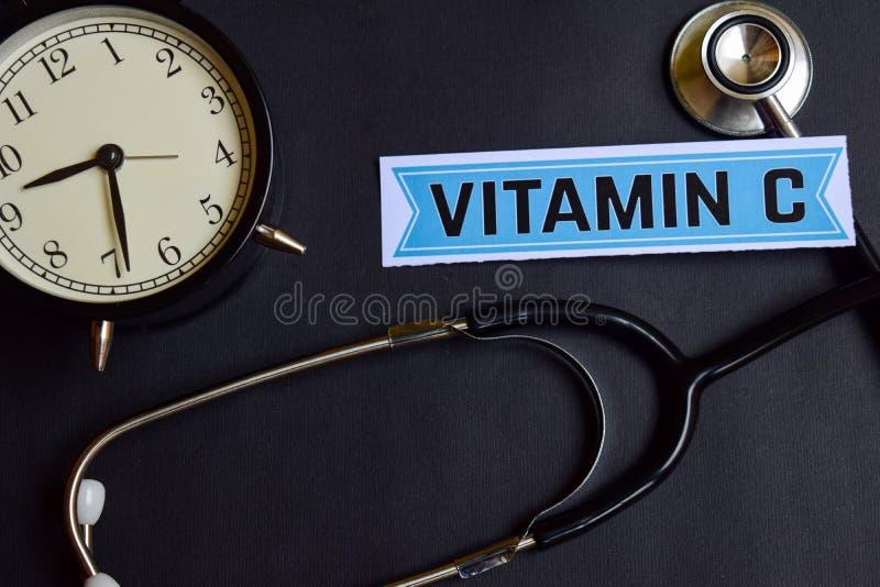 Vitamine C op het document met de Inspiratie van het Gezondheidszorgconcept wekker, Zwarte stethoscoop royalty-vrije stock afbeelding