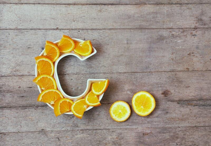 Vitamine C in voedselconcept Plaat in vorm van brief C met oranje plakken op houten achtergrond Vlak leg of hoogste mening royalty-vrije stock foto's