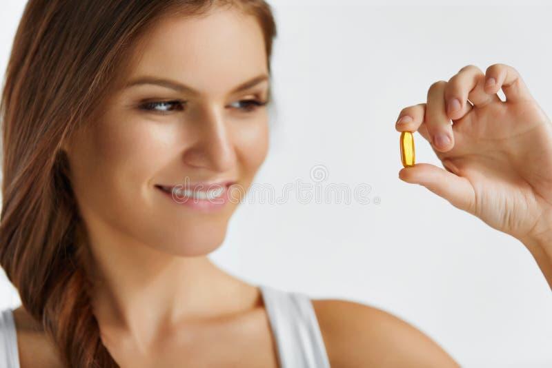 Vitamine Cibo sano Ragazza felice con i cappucci dell'olio di pesce Omega-3 immagine stock libera da diritti