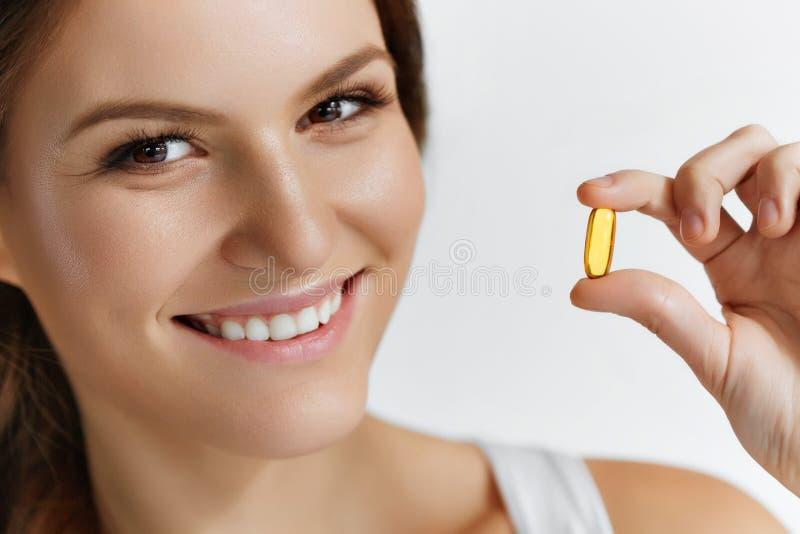 Vitamine Cibo sano Ragazza felice con i cappucci dell'olio di pesce Omega-3 fotografia stock libera da diritti