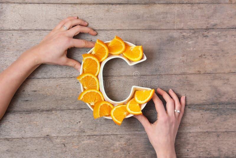 Vitamine Cvoedingsmiddel in voedselconcept Vrouwenhanden die plaat in vorm van brief C met oranje plakken op houten achtergrond h royalty-vrije stock afbeelding