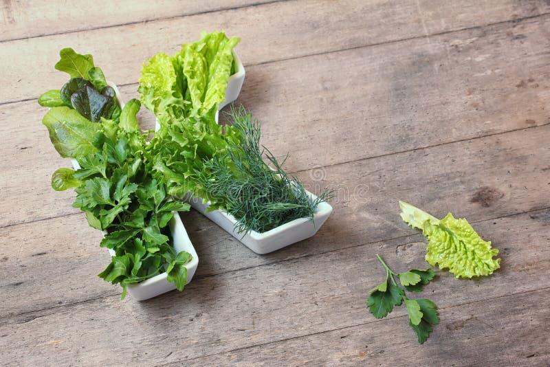 Vitamine K in voedselconcept De brief K vormde plaat met verschillende verse blad groene groenten, sla, kruiden op houten achterg royalty-vrije stock fotografie