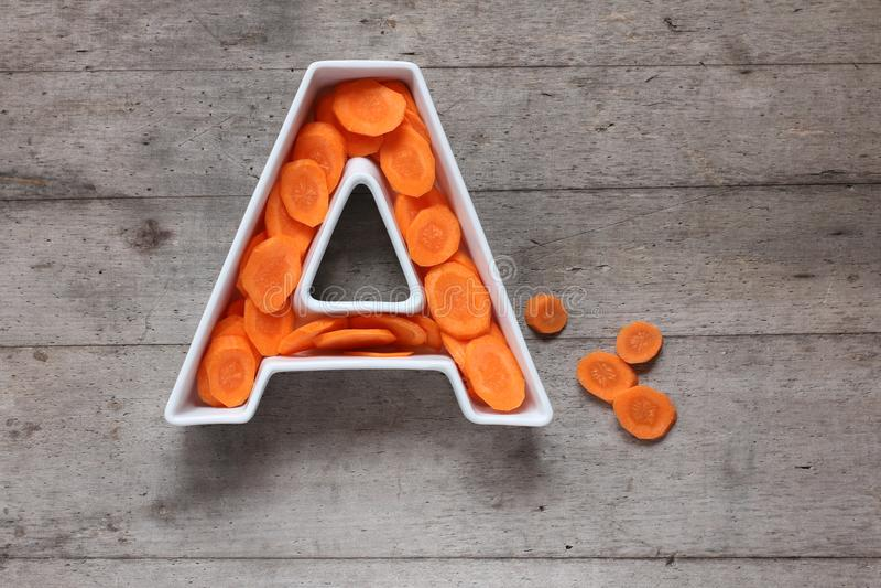 Vitamine A in voedselconcept Plaat in de vorm van de brief A met gesneden verse wortelen op houten achtergrond Vlak leg royalty-vrije stock foto's