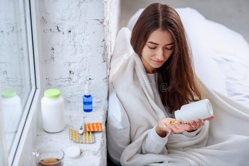 Vitaminen en Voedselsupplementenconcept Vrouw die gele pillen gieten uit fles in palm Vrouw die uit medicijn morsen stock foto