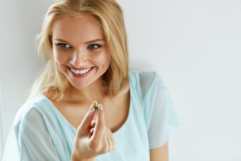 Vitaminer och mattillägg Härlig kvinna med preventivpilleren i hand arkivbild