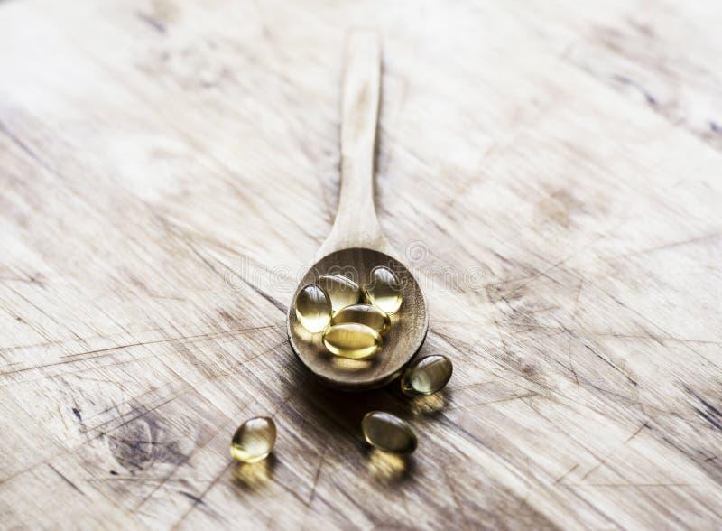 Vitamines dans une cuillère en bois photographie stock libre de droits