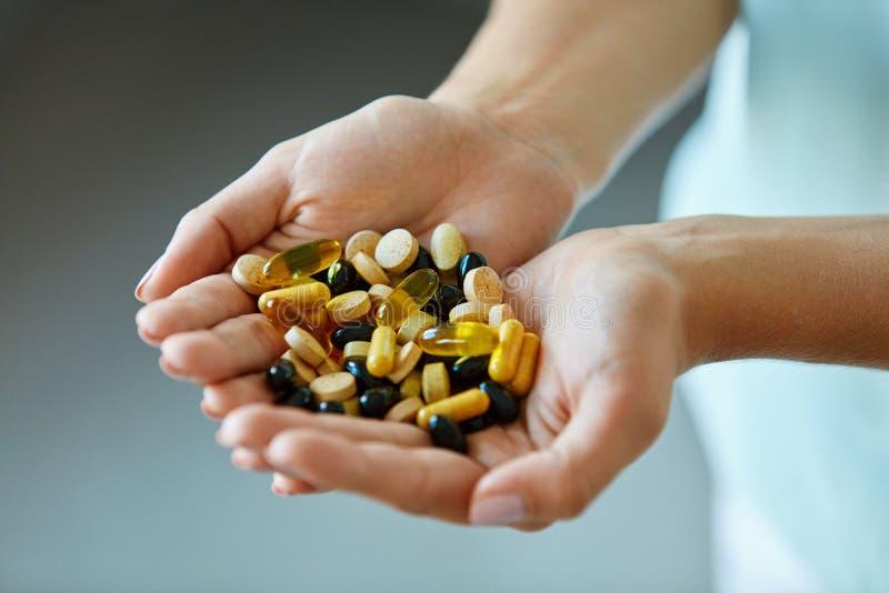 Vitamines et suppléments La femme remet complètement des pilules de médicament photographie stock libre de droits