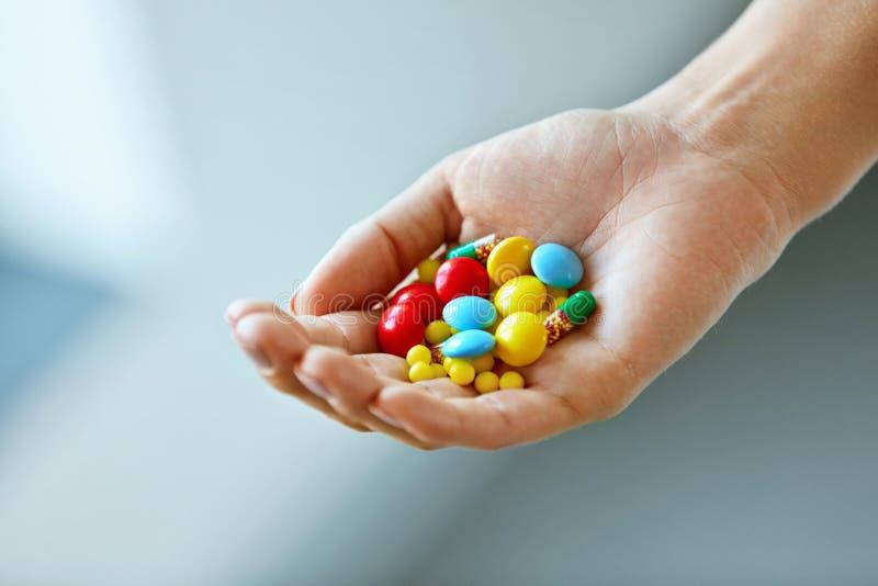 Vitamines et suppléments Main femelle avec les pilules colorées photographie stock libre de droits