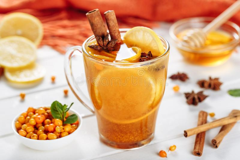 Vitaminic healthy sea buckthorn tea in small glass cup with fresh raw seabuckthorn berries, lemon, honey and cinnamon royalty free stock photos