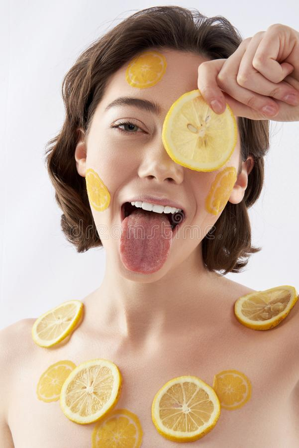 Funny happy woman with many lemon pieces stock photography