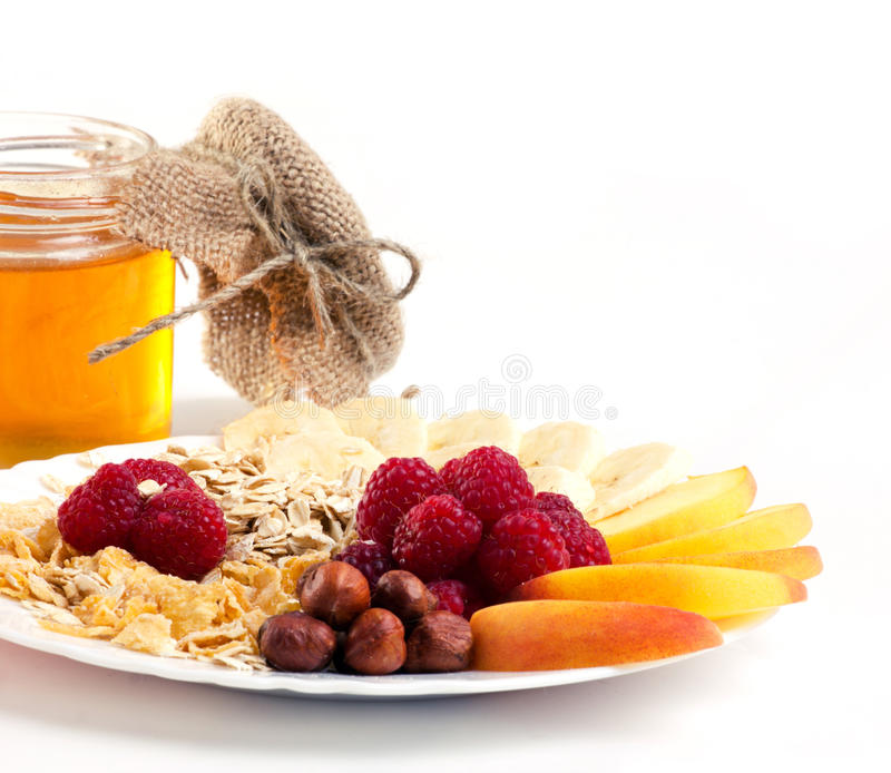 Vitamins breakfast. Muesli with berry, fruits, nuts and honey on white background royalty free stock photography