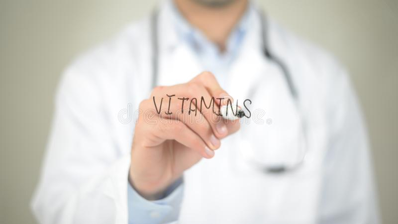 Vitamins, Doctor writing on transparent screen stock image