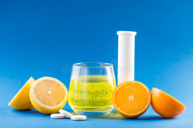 Vitamins with fruit flavor. Vitamin pills. Vitamins with fruit flavor. Vitamin C, lemon, orange, white conteiner for pills on blue background royalty free stock image