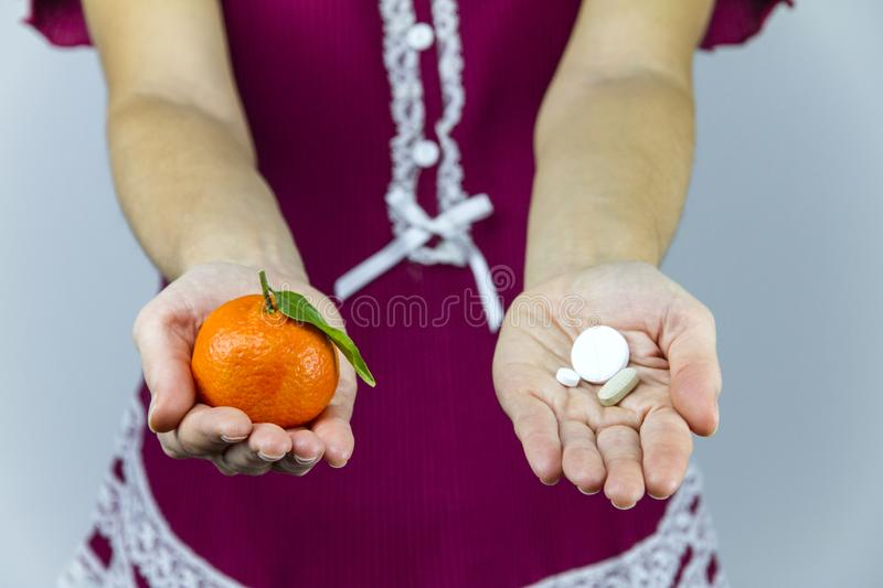 Vitamins from fruits or medicines? A young woman in burgundy pajamas shows a mandarin in her right hand and an aspirin in her left royalty free stock image