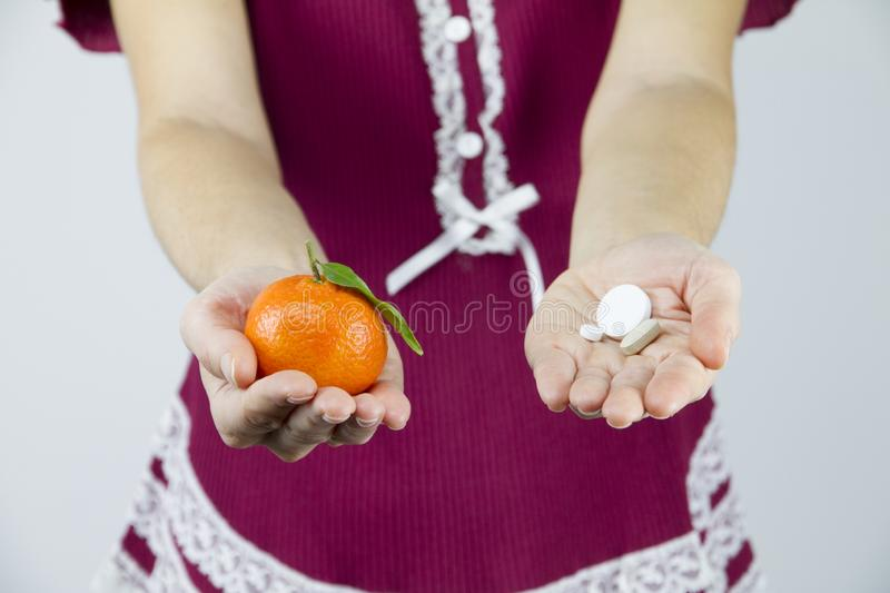 Vitamins from fruits or medicines? A young woman in burgundy pajamas shows a mandarin in her right hand and an aspirin in her left stock photography
