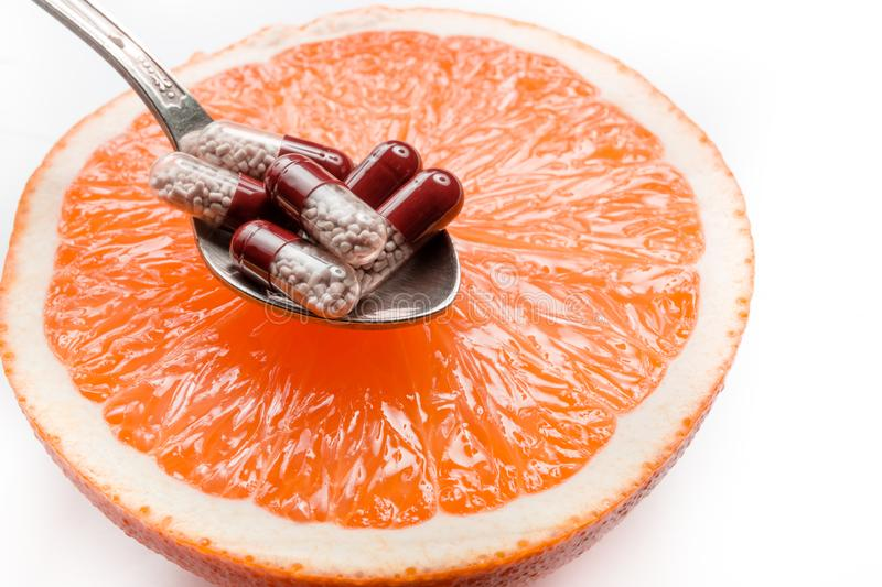 Vitamins in a spoon, lying on a grapefruit. stock images