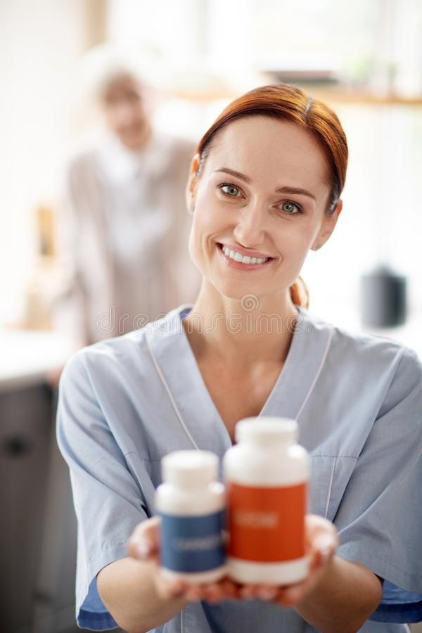 Caregiver holding vitamins and supplements for patient. Vitamins and supplements. Red-haired young caregiver holding vitamins and supplements for patient royalty free stock photography