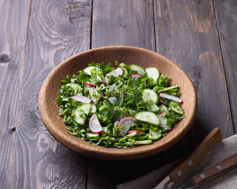 Vitaminsallad av lösa örter med gurkan, rädisan och salladslökar royaltyfria foton