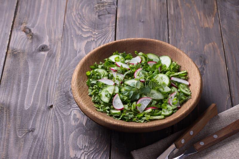 Vitaminsallad av lösa örter med gurkan, rädisan och salladslökar royaltyfri fotografi