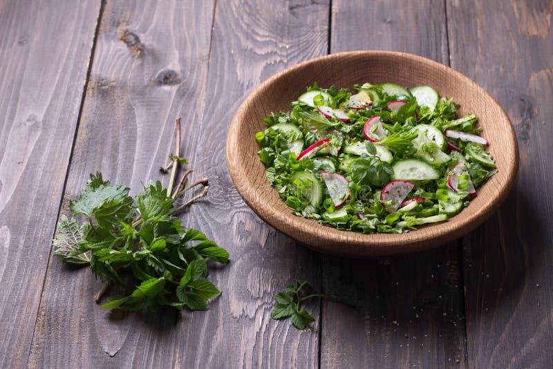 Vitaminsallad av lösa örter med gurkan, rädisan och salladslökar royaltyfri bild