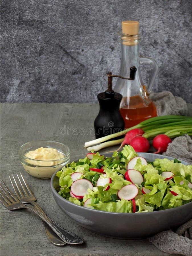 Vitaminsallad från grönsallat, rädisan, salladslökar och ägg som kryddas med grönsakolja och senap i platta på grå färger, hårdna royaltyfri bild