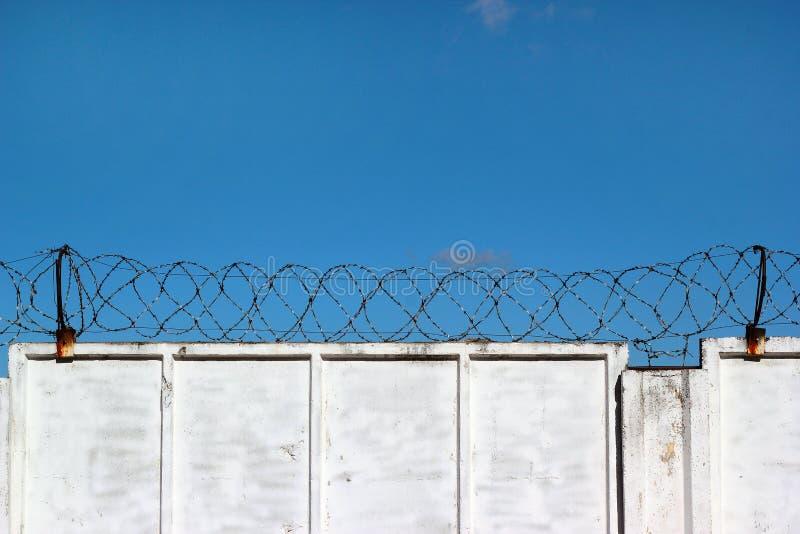 Vitbetongstaketet med försett med en hulling - binda mot en blå himmel fotografering för bildbyråer
