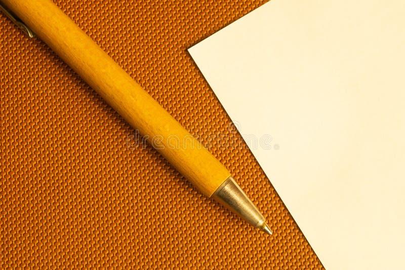 Vitbok med träpennan på en brun bakgrund arkivbild