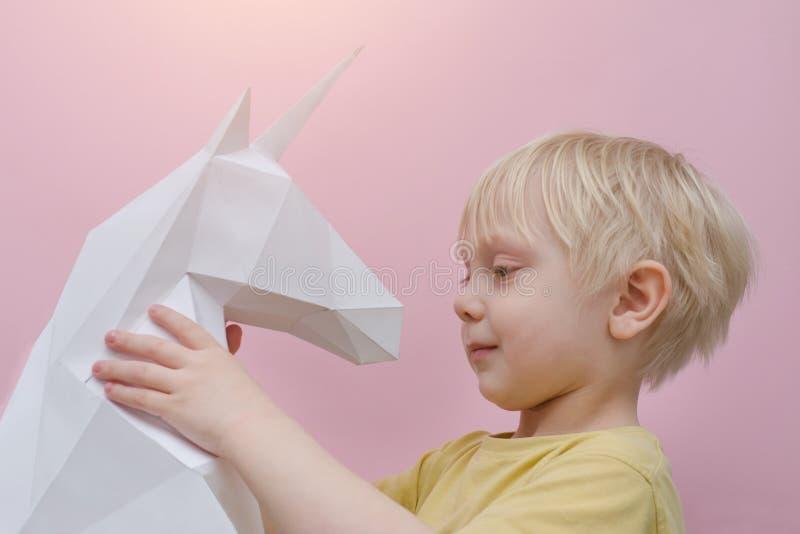 Vitbokenhörning och liten blond pojke Rosa bakgrund arkivbilder