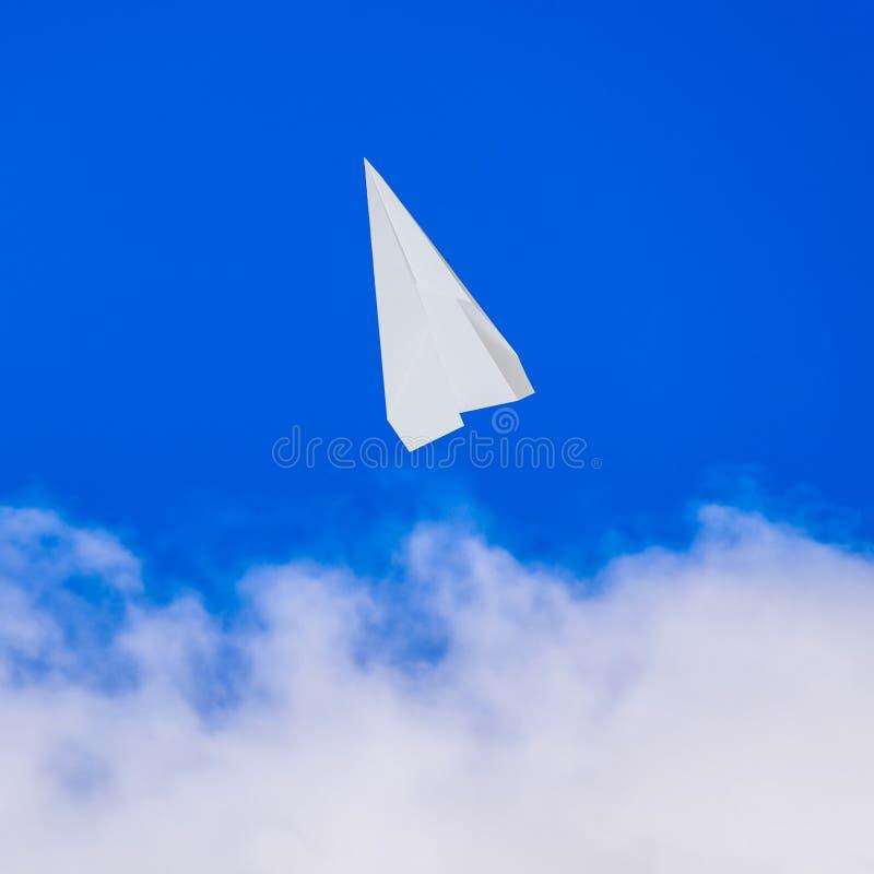Vitbokflygplan i en blå himmel med moln Meddelandesymben arkivbilder