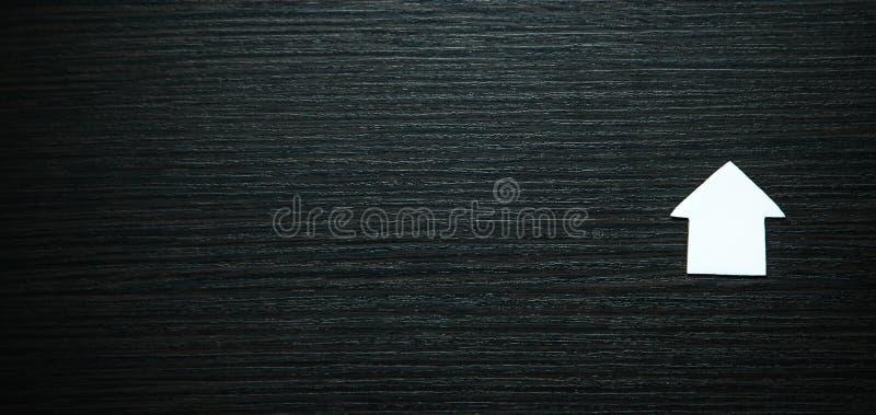 Vitbokhus på svart träbakgrund verkligt begreppsgods arkivfoto