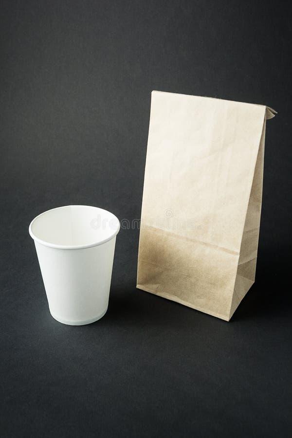 Vitbokkopp för te, kaffe eller fruktsaft som framläggas nära den mellanrum återanvända pappers- påsen som isoleras på svart bakgr arkivfoton