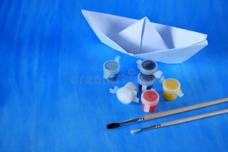 Vitbokskepp, målarfärger av olika färger och borstar royaltyfri bild