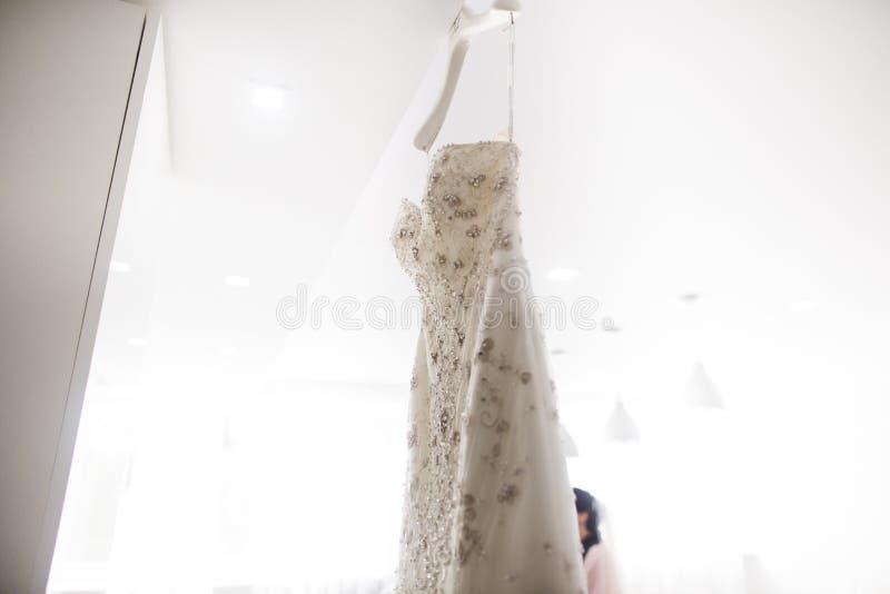 Vitbröllopsklänningen som hänger på a, knuffar royaltyfria foton