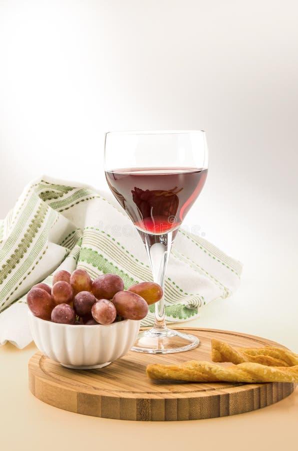 Vite rossa in un vetro con l'uva e il grissini 2 immagine stock libera da diritti