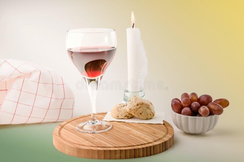 Vite rossa in un vetro con l'uva e la candela fotografia stock libera da diritti