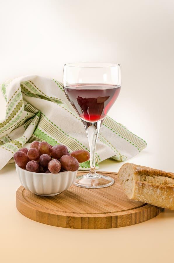 Vite rossa in un vetro con pane e l'uva immagini stock